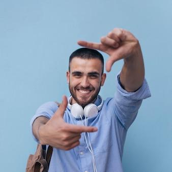 Portret die van de glimlachende mens kader met zijn hand maken tegen blauwe achtergrond