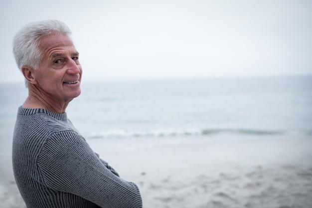 Portret die van de hogere mens zich met die wapens bevinden op strand worden gekruist