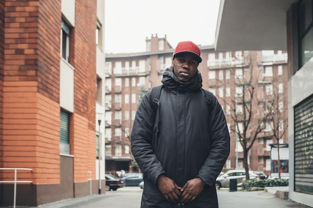 Portret die van de jonge afrikaanse zich in de straat bevinden en camera kijken