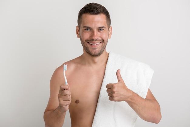 Portret die van de jonge glimlachende mens duim op gebaar tonen terwijl het houden van tandenborstel