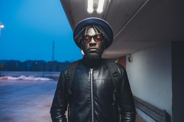 Portret die van de jonge zwarte mens zich in de straat bevinden