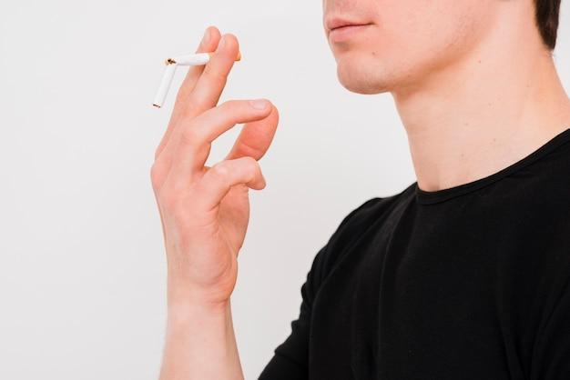 Portret die van de mens gebroken sigaret op witte muur houden