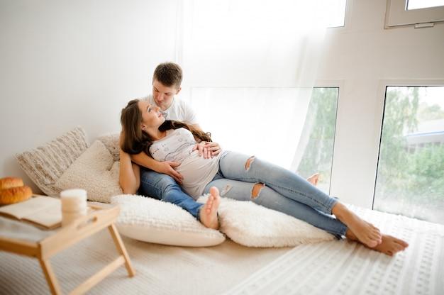 Portret die van de mens met mooie zwangere vrouw op het bed in een witte ruimte liggen