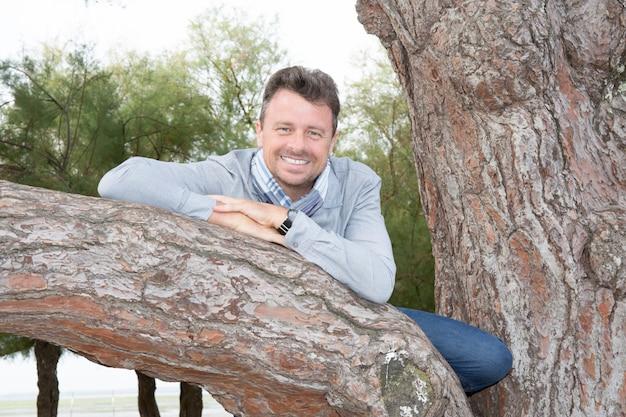 Portret die van de mens op middelbare leeftijd zich tegen boom bevinden