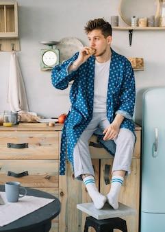 Portret die van de mens voedsel voor de zitting van het ochtendontbijt op keukenteller eten
