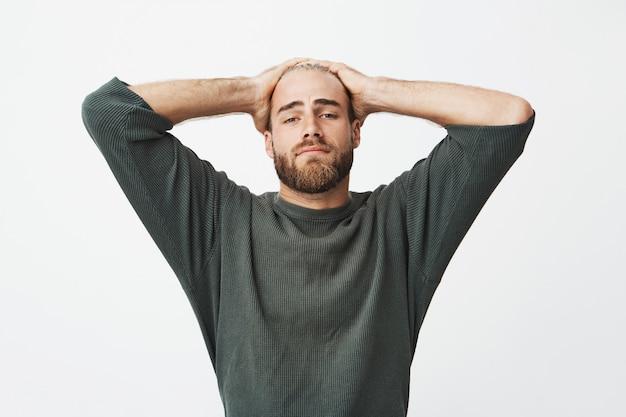 Portret die van de vermoeide knappe handen van de mensenholding op hoofd, terug op stoel leunen te rusten