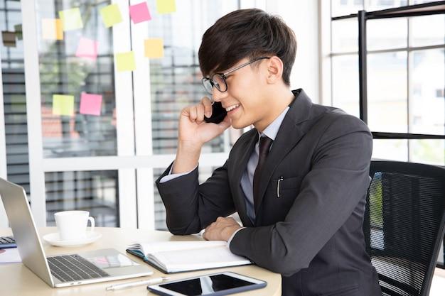 Portret die van een glimlachende jonge zakenman op zijn smartphone spreken terwijl hij die aan zijn computer werkt, in zijn bureau bij bureau zit dat een zwart kostuum draagt.