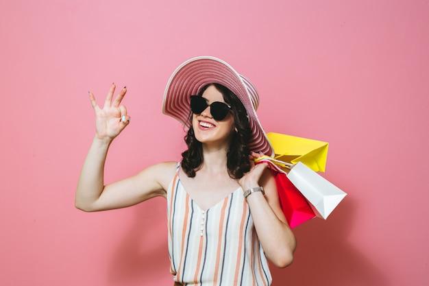Portret die van een mooi meisje die met zonnebril glimlachen, het winkelen zakken en geldbankbiljetten over roze achtergrond houden