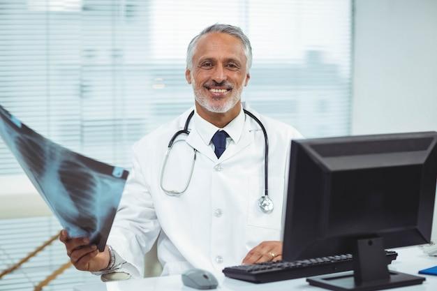 Portret die van gelukkige arts x-ray in kliniek houden