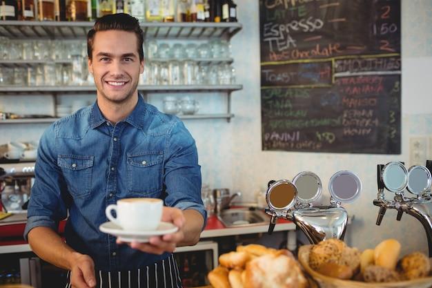 Portret die van gelukkige eigenaar koffie aanbieden bij cafetaria