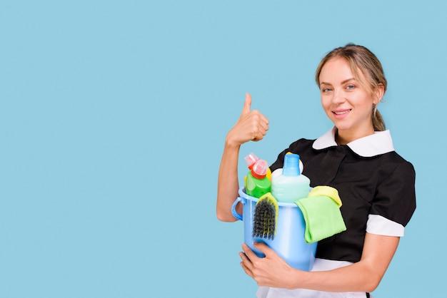 Portret die van gelukkige huishoudster duim op het schoonmakende materiaal van de gebaarholding tonen in emmer die camera bekijken