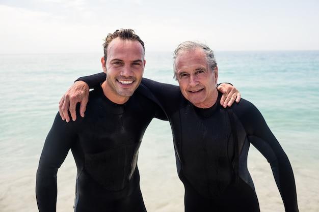 Portret die van gelukkige vader en zoon in wetsuit op het strand omhelzen