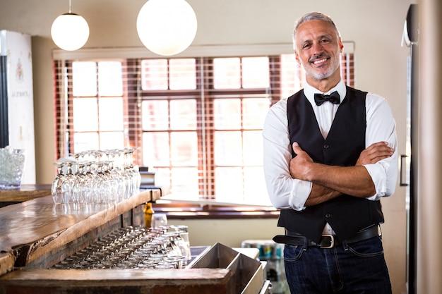 Portret die van glimlachende barman zich met gekruiste wapens bevinden