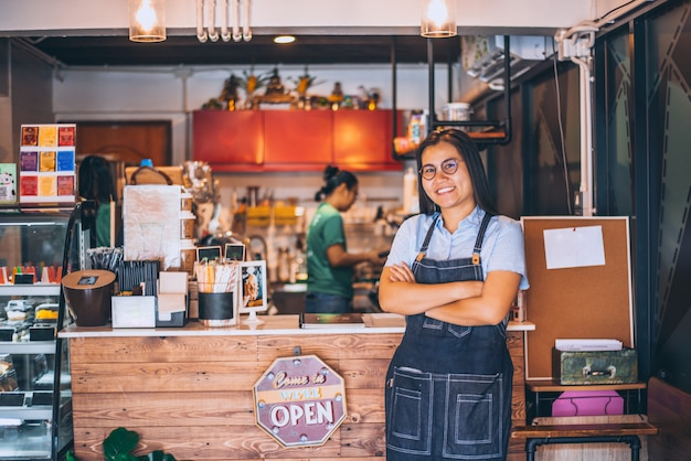 Portret die van glimlachende eigenaar zich bij koffiewinkel bevinden, klein familiebedrijf. portret die van glimlachende eigenaar zich bij voor tegenbar bevinden