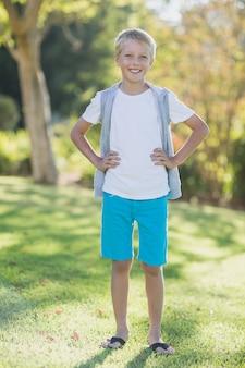 Portret die van glimlachende jongen zich met hand op heup in park bevinden