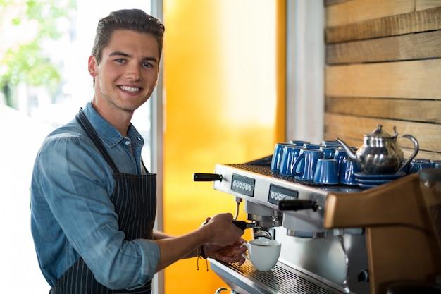 Portret die van glimlachende kelner kop van koffie maken bij teller