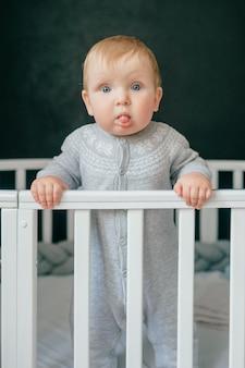 Portret die van grappige baby zich in voederbak bevinden.
