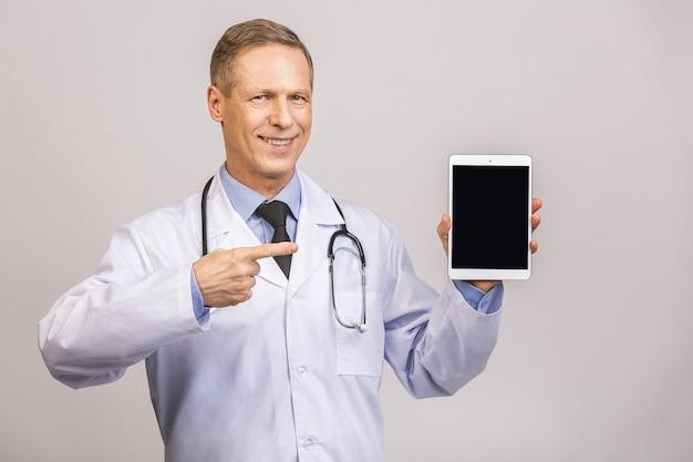 Portret die van hogere gelukkige arts het lege scherm van de tabletcomputer tonen dat over grijze muur wordt geïsoleerd.