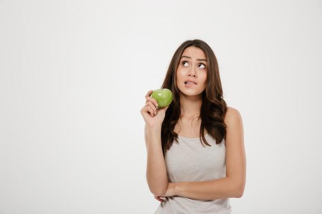 Portret die van in verwarring gebrachte vrouw stijgend het houden van groene verse appel kijken, die over gezond voedsel denken dat over wit wordt geïsoleerd