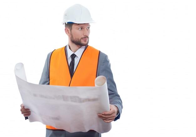 Portret die van ingenieur in oranje vest en witte veiligheidshoed dragen die groot tekeningsplan houden.