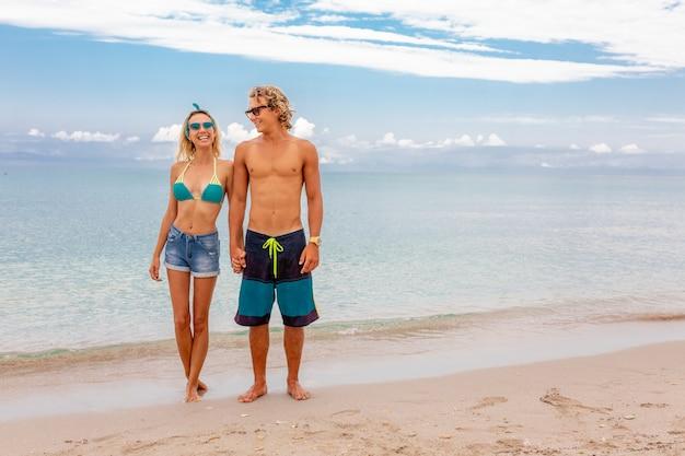 Portret die van jong paar in liefde bij strand omhelzen en van tijd genieten die samen zijn. idealistische artistieke fotoposter voor reclamebanner