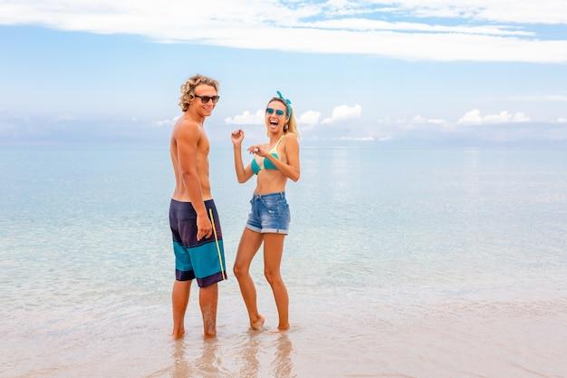 Portret die van jong paar in liefde bij strand omhelzen en van tijd genieten die samen zijn. jong koppel plezier op een zandige kust