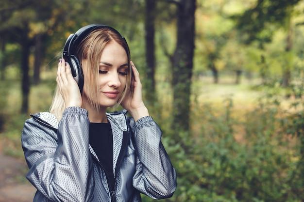 Portret die van jonge aantrekkelijke blondevrouw op een stadspark, aan muziek op hoofdtelefoons luisteren