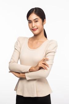 Portret die van jonge aziatische bedrijfsvrouw zich met gekruiste wapens bevinden en camera bekijken die op witte achtergrond wordt geïsoleerd