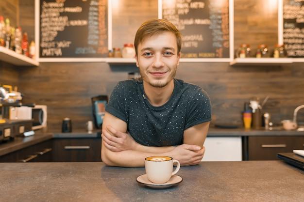 Portret die van jonge glimlachende mannelijke koffiearbeider, zich bij de teller bevinden