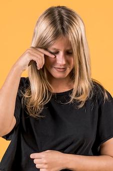 Portret die van jonge huilende vrouw zich voor gele muur bevinden