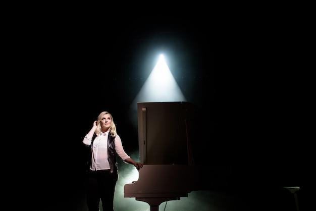 Portret die van jonge kaukasische vrouw zich dichtbij de grote piano bevinden