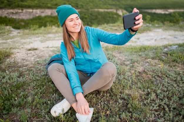 Portret die van jonge vrouw een selfie in openlucht nemen