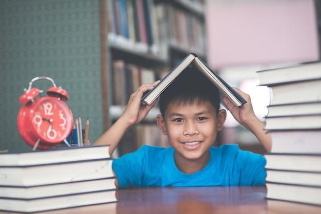 Portret die van jongen zeer gelukkig in de bibliotheek de dagtijd bekijken. concept schoolthema.