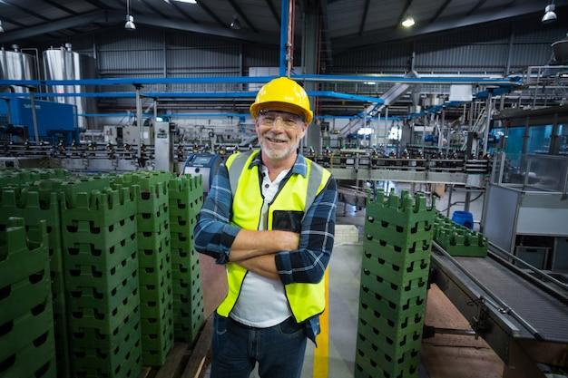 Portret die van mannelijke fabrieksarbeider zich met gekruiste wapens bevinden