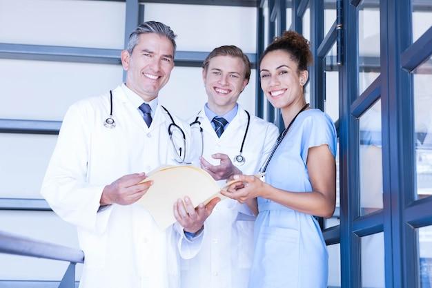 Portret die van medisch team zich en bij camera in het ziekenhuis verenigen glimlachen