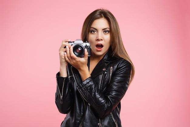 Portret die van modieus meisje oude camera houden, verbaasd verrast kijken