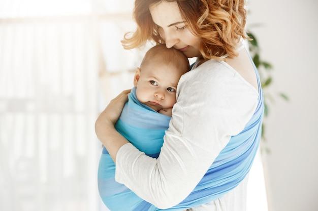Portret die van mooie jonge moeder haar pasgeboren babyjongen met liefde en zorg strak houden. ze glimlacht en voelt het geluk van de moedermomenten.