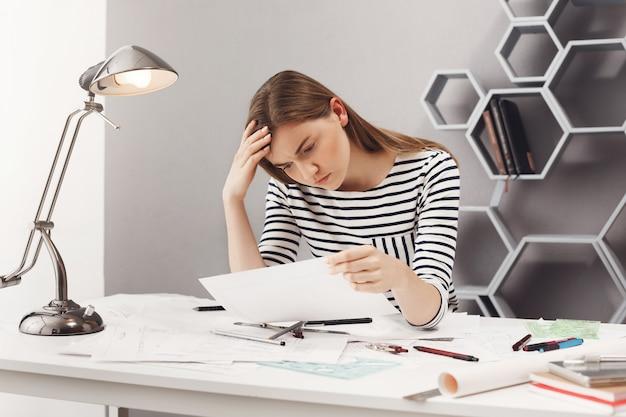 Portret die van mooie jonge ongelukkige vrouwelijke ingenieur aan witte lijst in comfortabele coworkingruimte zitten, die documenten met verstoorde uitdrukking bekijken die droevig zijn na het vinden van fout in blauwdrukken.