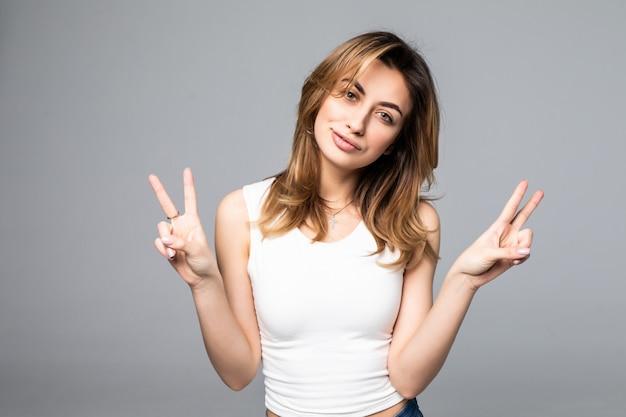 Portret die van mooie jonge vrouw twee vingers of overwinningsgebaar, op grijze muur, met leeg copyspacegebied tonen voor tekst of slogan