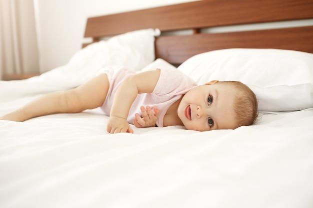 Portret die van mooie leuke pasgeboren baby tong tonen die thuis op bed liggen.