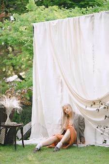 Portret die van mooie vrouw bij tuin, ter plaatse zitten en in oranje kleding en jasje overdag kijken.