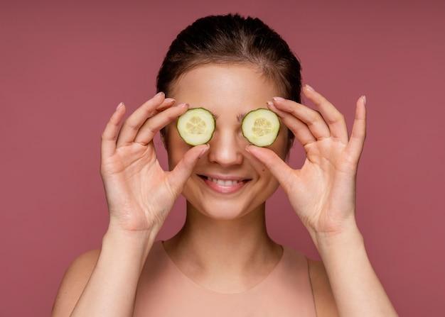 Portret die van mooie vrouw haar ogen behandelen met plakjes komkommer