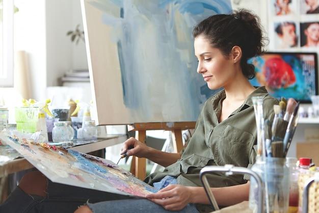 Portret die van mooie vrouwelijke kunstenaar in vrijetijdskleding, heldere kleuren mengen, op schildersezel trekken terwijl het zitten in kunststudio. brunette vrouwelijke schilder op het werk. creativiteit, kunst, schilderconcept