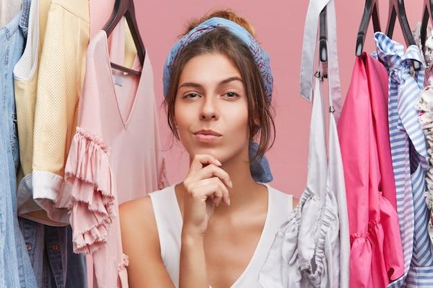 Portret die van nadenkende vrouw met sjaal op hoofd, zich dichtbij hangers met kleren bevinden, nadenken over wat te kopen. vrouwelijke shopaholic in boetiek met peinzende uitdrukking, met moeilijke keuze
