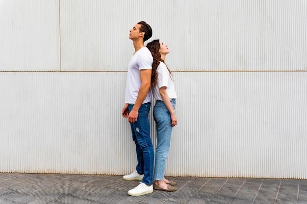 Portret die van ongelukkig gefrustreerd paar zich rijtjes bevinden die aan elkaar niet spreken na een argument terwijl status op grijze achtergrond