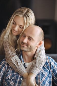 Portret die van paar op bank thuis omhelzen