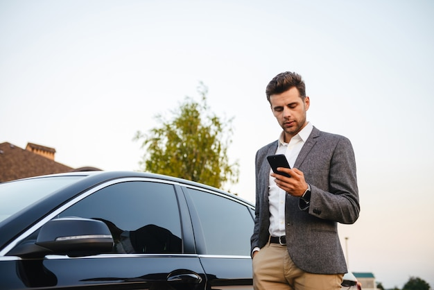 Portret die van rijke zakenman kostuum dragen, zich dichtbij zijn luxe zwarte auto bevinden, en smartphone gebruiken terwijl in hand het houden