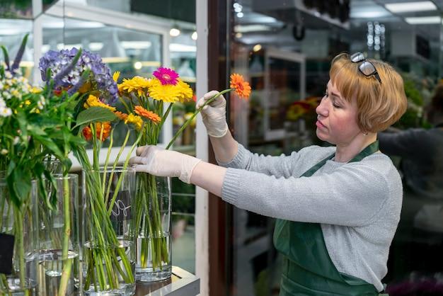 Portret die van rijpe vrouw bloemen behandelen