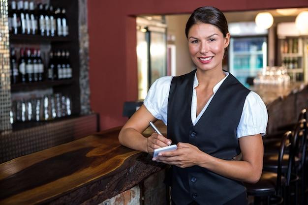Portret die van serveerster orde in restaurant nemen