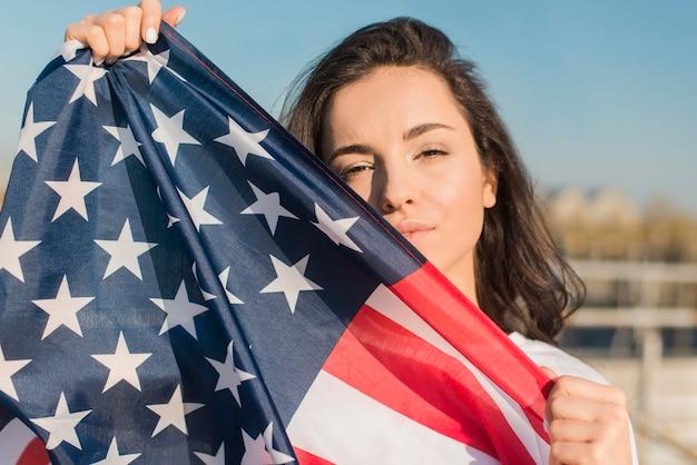 Portret die van vrouw de grote vlag van de vs houden